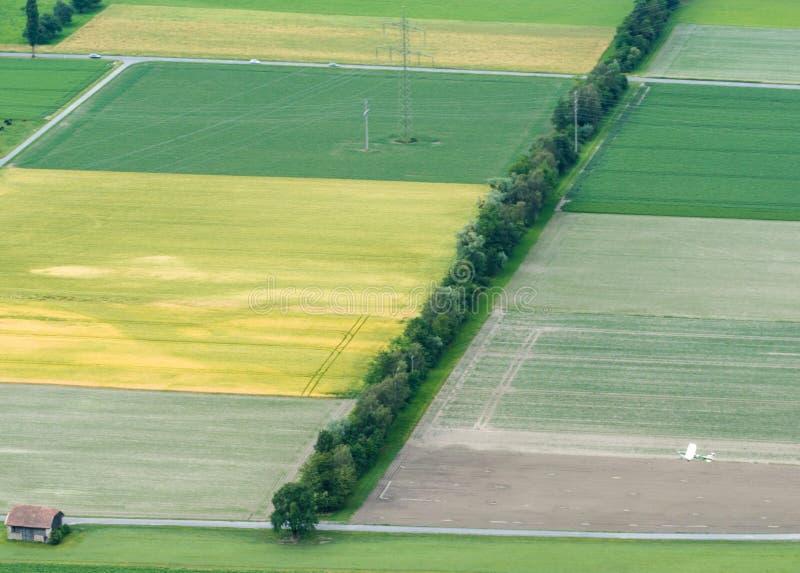 Uprawiający ziemię pola i rzędy drzewa z uprawy duster samolotem widzieć od above obraz stock
