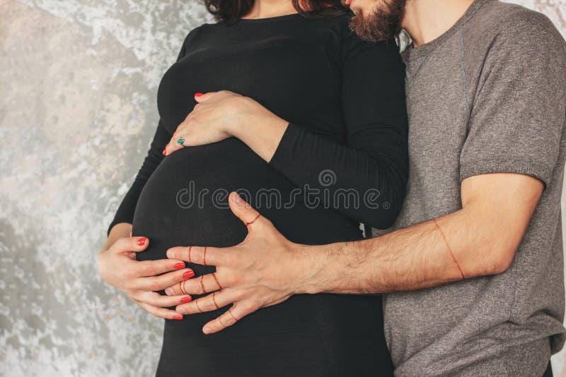 Uprawy fotografia ciężarna młoda kobieta w czerni sukni z mężem Autentyczna nadzwyczajna para, rodzinny czekać na dziecko zdjęcia royalty free