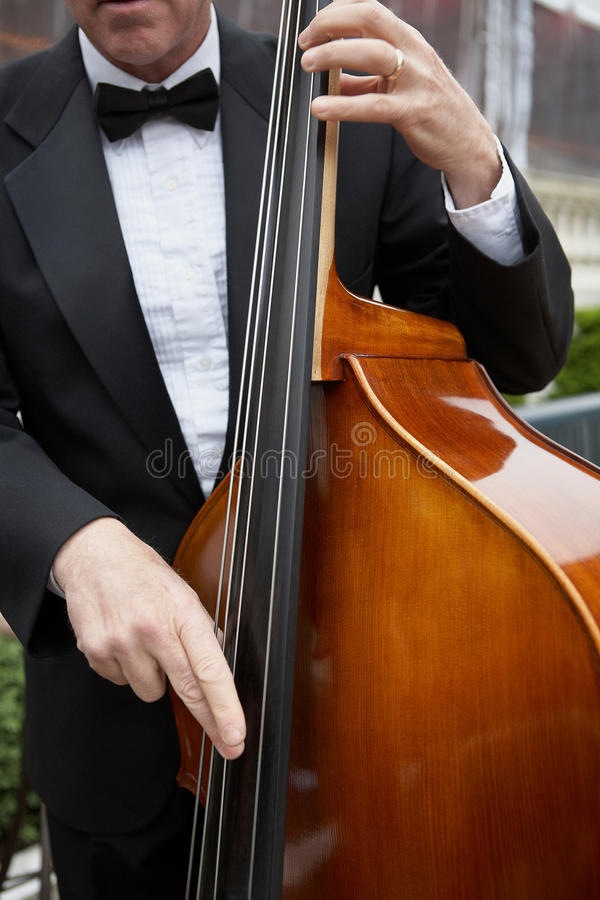 Upright bass musician. Jazz musician playing upright bass at luxury party stock photography