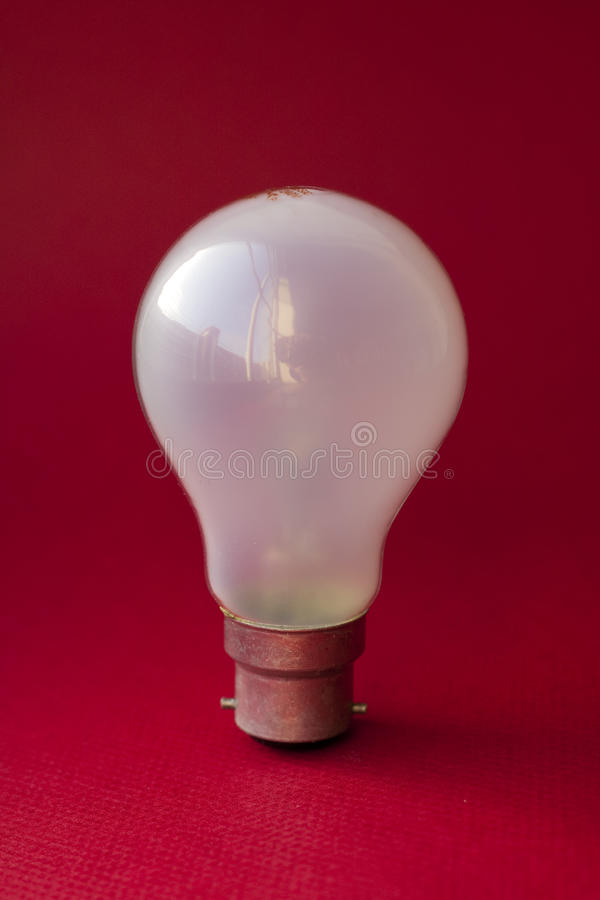 Upright lightbulb. Standard 60w bayonet tungsten lightbulb against a red background stock photography