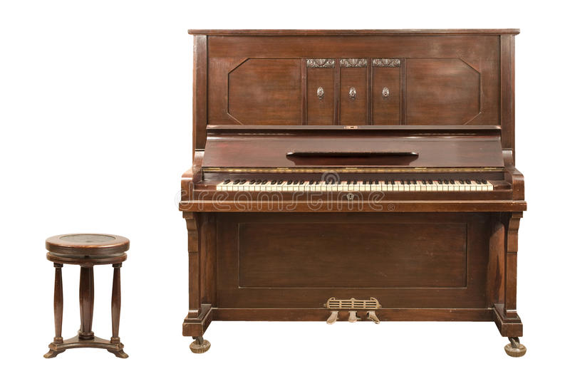 Upright Piano. Old upright german piano and a stool isolated over white background. Clipping paths included royalty free stock photo
