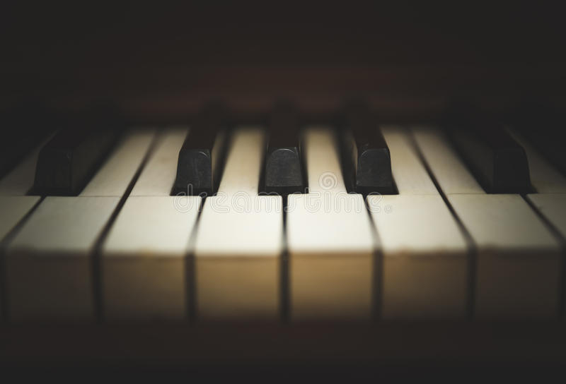 Upright piano keyboard or piano keys. Close-up view of keys on an antique, wooden, upright piano royalty free stock photo