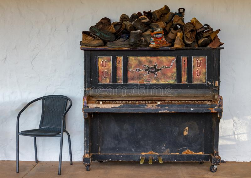 Upright piano, lost shoes and a chair. Old upright piano covered in lost shoes near a chair stock image