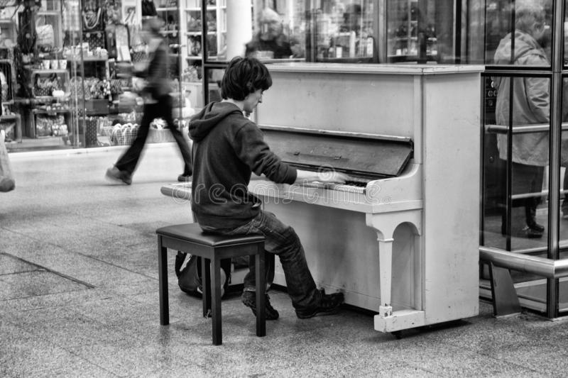 Music student playing to passers by at St. Pancras royalty free stock photo