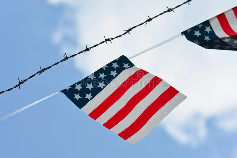 Uproszczona flaga z amerykan kolorami z czerwień lampasami i białe gwiazdy na błękitnym tła obwieszeniu obok drutu kolczastego my fotografia royalty free
