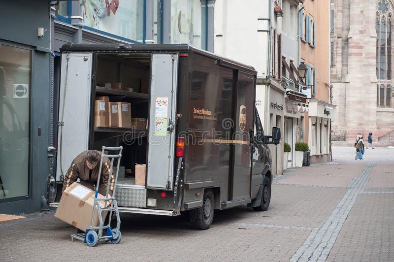 UPS卸载从他的卡车的交付工作者包裹在街道 库存图片
