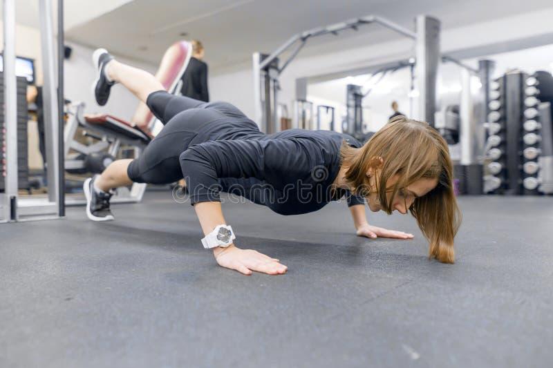 Νέα γυναίκα ικανότητας που επιλύει κάνοντας το ώθηση-UPS στο πάτωμα στην αθλητική γυμναστική Αθλητισμός, ικανότητα, κατάρτιση, τρ στοκ φωτογραφία