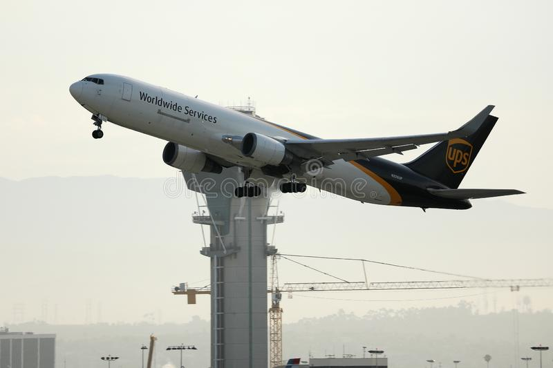 UPS Airlines plane taking off from Los Angeles Airport, LAX. ATC air traffic control tower on background stock photography