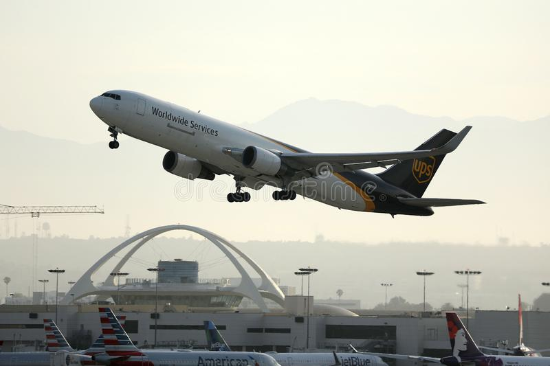 UPS Airlines plane taking off from Los Angeles Airport, LAX. ATC air traffic control tower on background stock photo