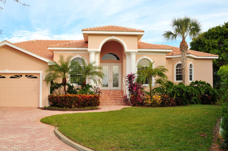 Upscale house with luxurious tropical landscaping stock photo