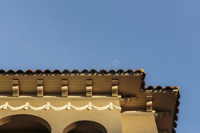 Upscale house roof and cornice detail. Detail of the roof and cornice of an upscale modern home against a clear blue sky stock images