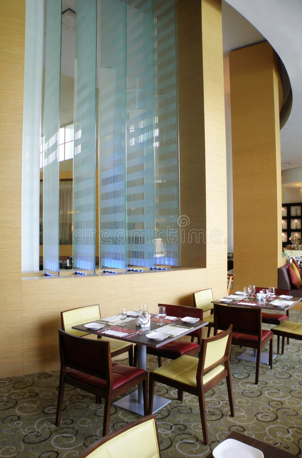 Upscale restaurant setting. An image showing interior of an expensive restaurant, with high ceiling, modern contemporary glass and wood decor, and lush carpeting royalty free stock image