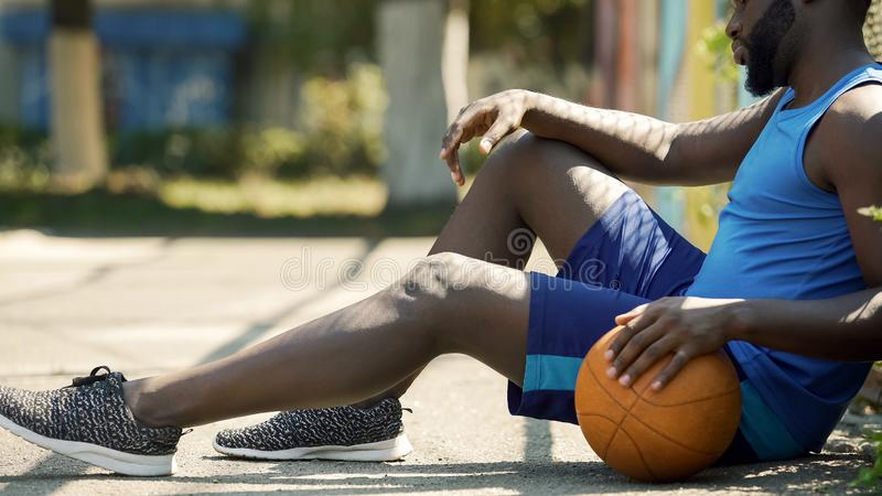 Upset African American basketball player sitting on ground, holding ball royalty free stock photo