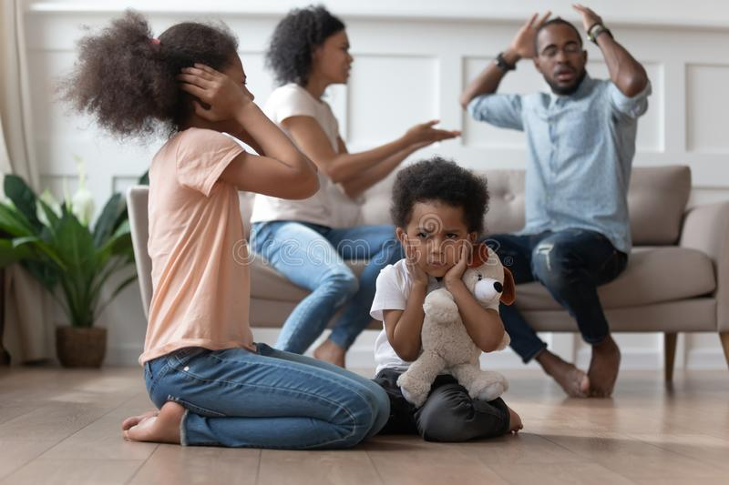 Upset african kids closing ears hurt by parents fighting. Arguing at home, sad stressed little innocent children suffer from family problems conflicts, unhappy royalty free stock image