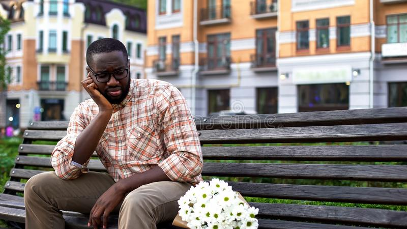 Upset afro-american man sitting lonely on city bench with bouquet, failed date stock photography