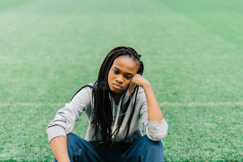 The upset afro-american teenager is sitting on the grass and leaning on her hand. royalty free stock photo