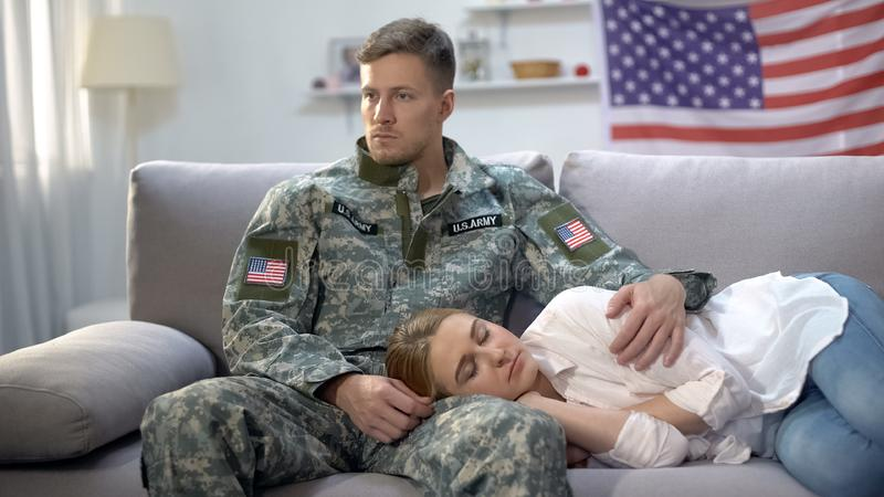 Upset american soldier stroking girlfriend sleeping on sofa, military service. Stock photo stock images