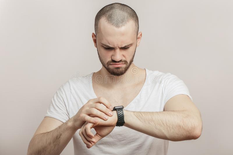 Upset, angry athlete with heart rate monitor watch. stock photos