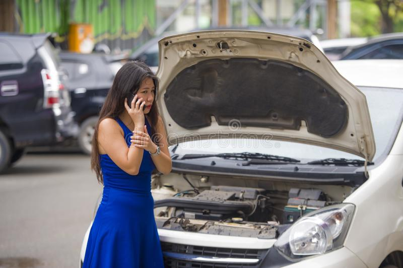 Upset Asian Japanese woman in stress stranded on street suffering car engine failure having mechanic problem calling on mobile royalty free stock images