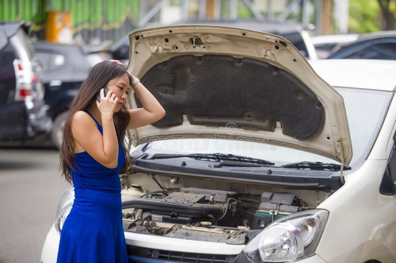 Upset Asian Korean woman in stress stranded on street suffering car engine failure having mechanic problem calling on mobile phone. Young desperate and upset royalty free stock image
