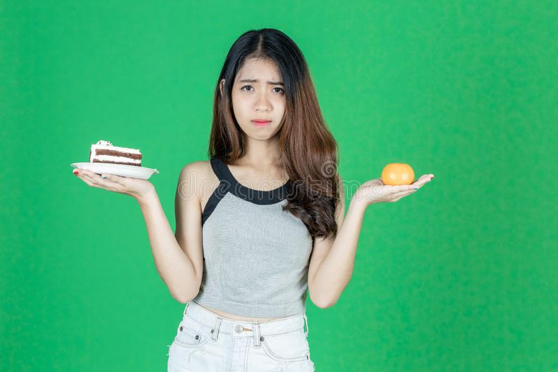 Upset Asian woman choosing between orange fruit or unhealthy cake on hands over green  background. Healthy lifestyle and. Dieting concept royalty free stock image
