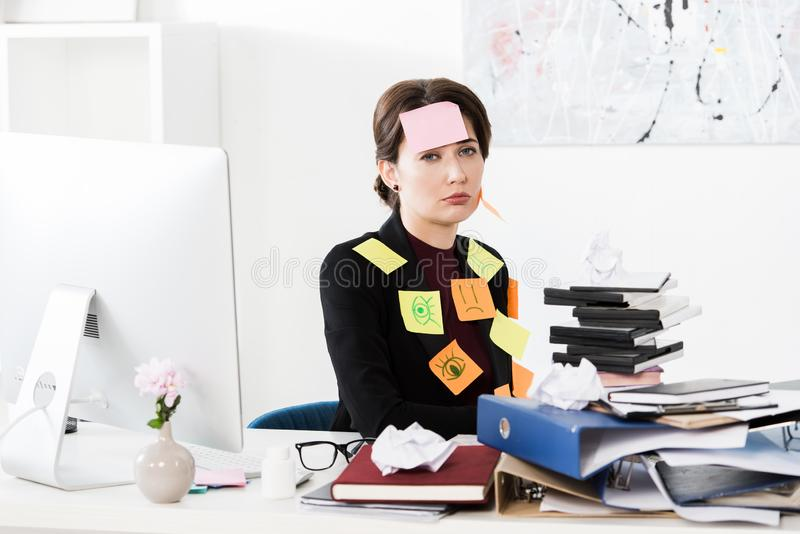 Upset attractive businesswoman sitting with stickers on face and clothes in office, looking stock photography