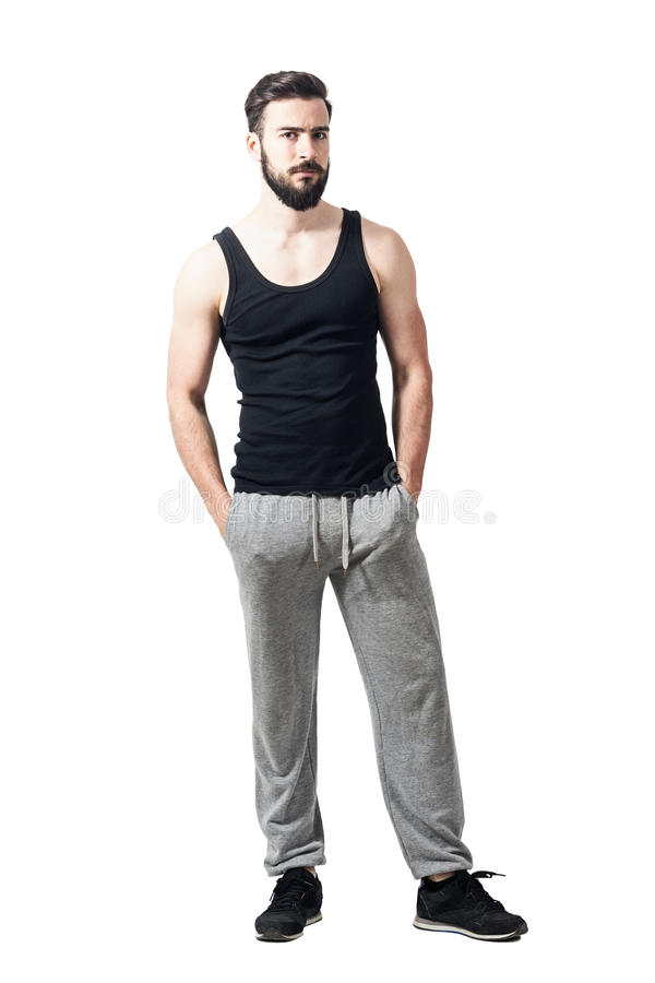 Upset bearded athlete in tank top and jogger pants looking at camera. Toned desaturated full body length portrait isolated on white studio background royalty free stock photo