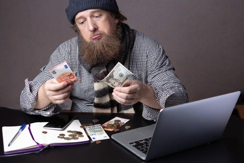 Upset Bearded Man in knitted hat counting money, sitting beside notebook and notepad, having financial problems. Money concept stock images