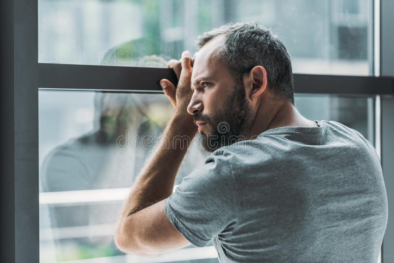 upset bearded man leaning at window and looking through it royalty free stock photos