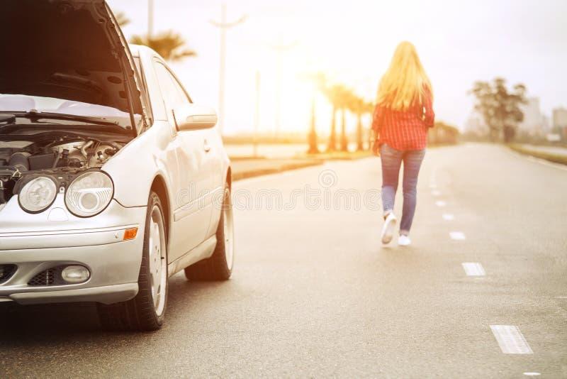 Upset blonde woman leaving her broken roadster royalty free stock photos