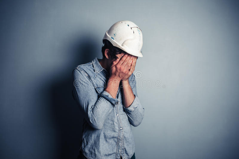Upset blue collar worker. An upset blue collar worker is burying his face in his hands stock photo