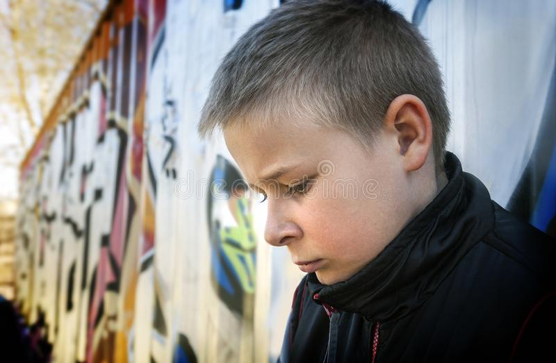 Upset boy against a wall royalty free stock images
