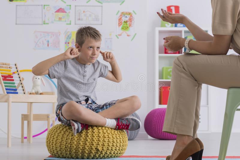 Upset boy covering ears. Young upset boy covering ears during therapy session with child psychologist royalty free stock photos