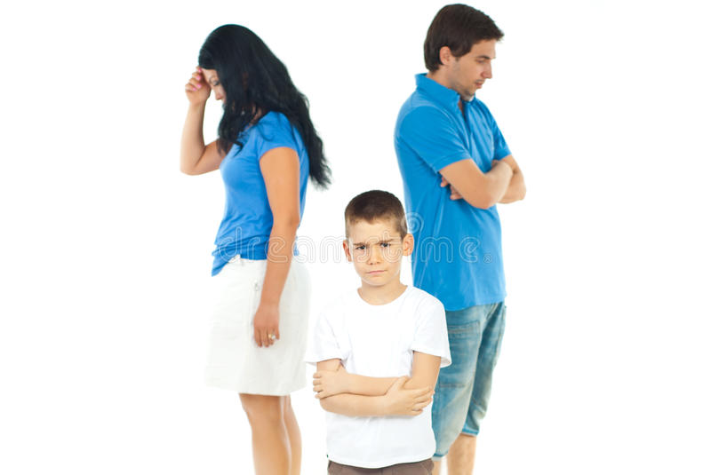 Upset boy between parents problems. Upset boy standing with arms folded in front of parents with problems against white background