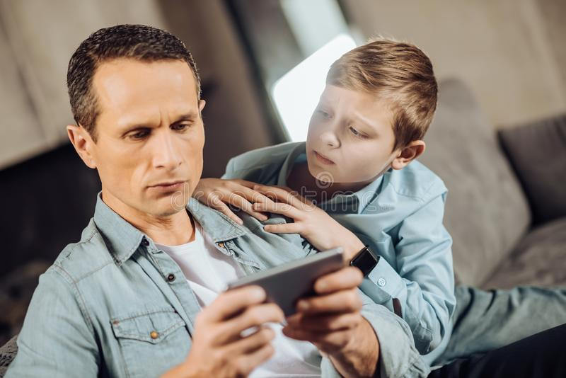 Upset boy searching attention from his father. Notice me. Sad pre-teen boy searching attention from his father and cuddling to him while the men playing on the royalty free stock photo