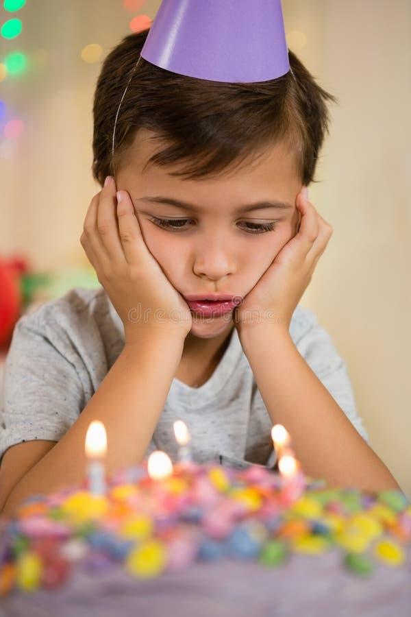 Upset boy sitting with birthday cake. At home stock image