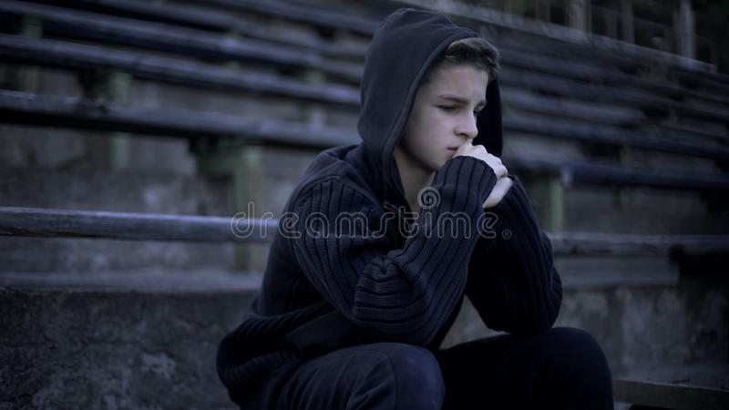 Upset boy sitting on stadium tribune, feels depression, loneliness and sorrow royalty free stock photos