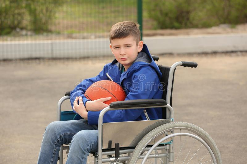 Upset boy in wheelchair with ball on ground royalty free stock photography
