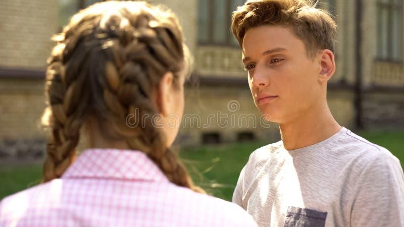 Upset boyfriend looking at girlfriend, relationship difficulties, break up. Stock photo stock images