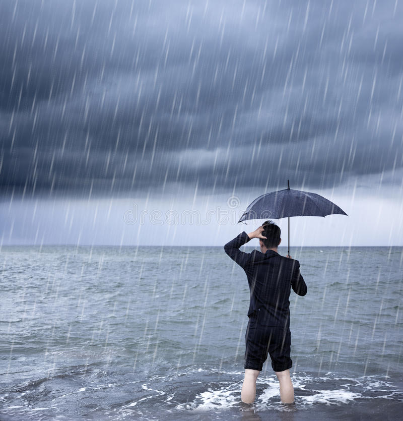 Upset business man holding a umbrella with cloudburst. Background royalty free stock photography