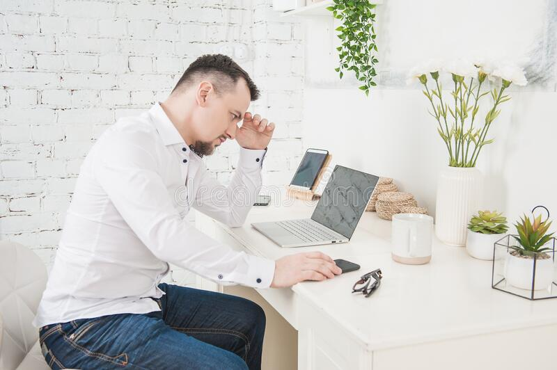 Upset Business man using laptop at home. Freelance or distance study concept royalty free stock photos