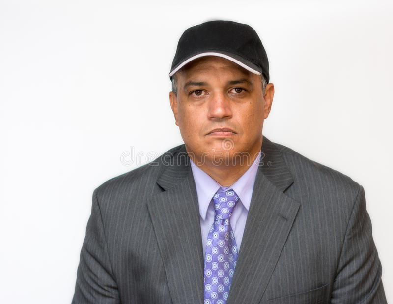 Upset business man wearing a suit and a cap. Disgruntled white collar employee over a white background royalty free stock photos