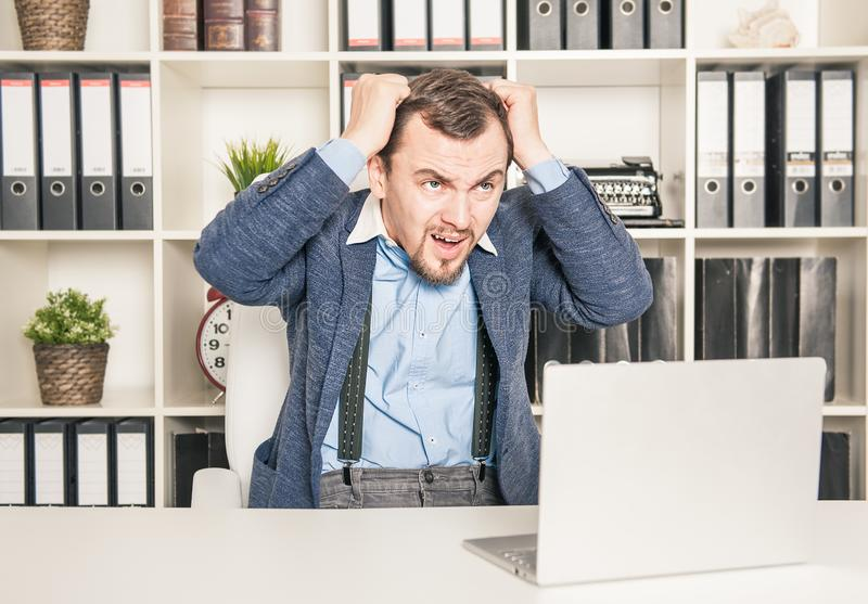 Upset business man working in office. Stress concept. Upset young business man working in office. Stress concept royalty free stock photos
