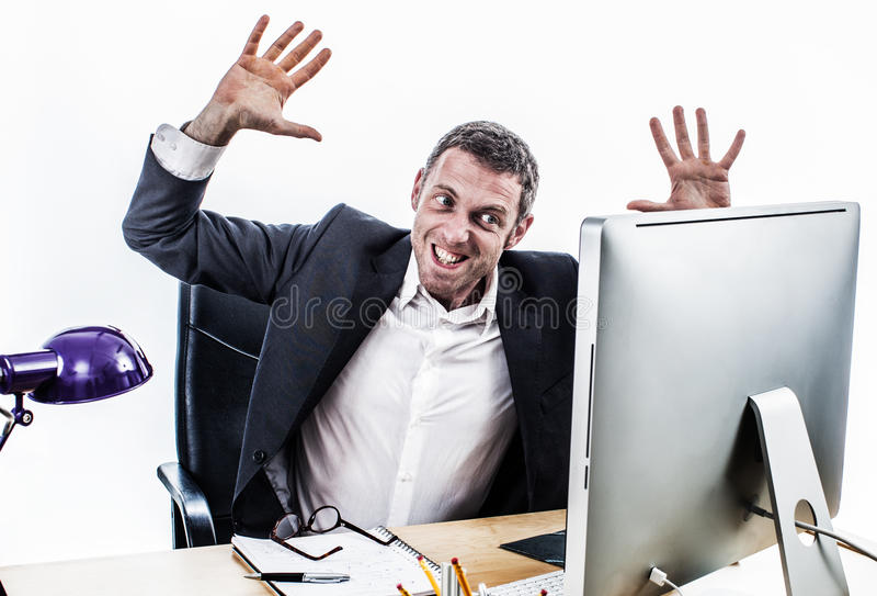 Upset businessman having a corporate tantrum at his computer desk stock photos