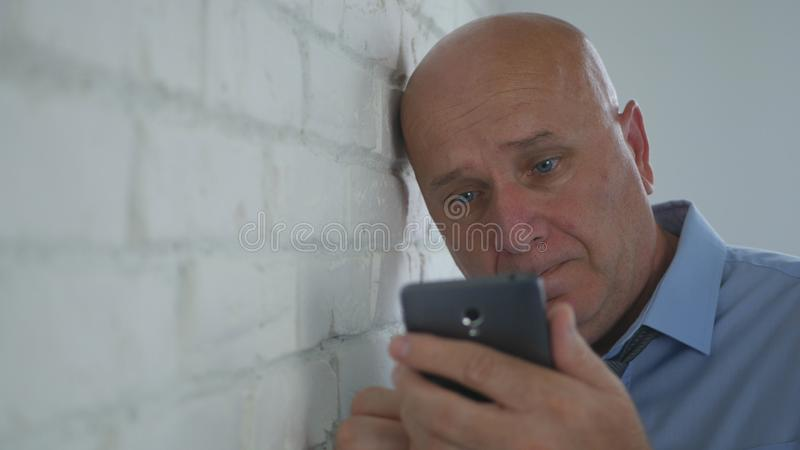 Upset Businessman Looking Disappointed on Cell Phone Text. Image with Upset Businessman Looking Disappointed on Cell Phone Text royalty free stock photography
