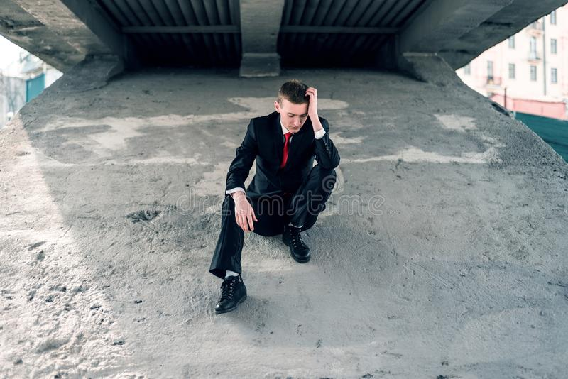 Upset businessman. Man failed. A young guy in a suit is sitting under a bridge. royalty free stock images