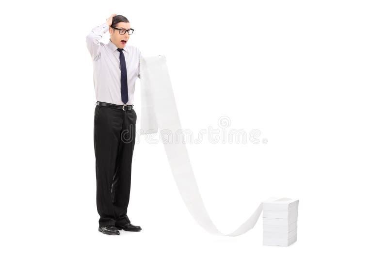 Upset businessman reading a long list stock photos