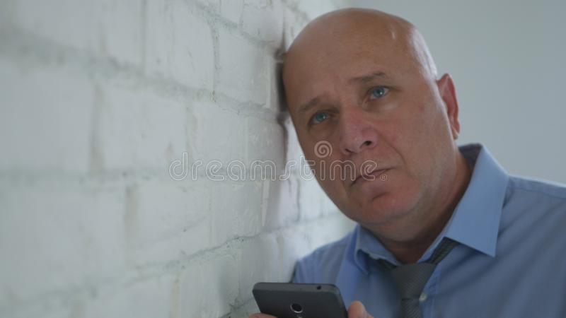 Upset Businessman Thinking Disappointed with Cell Phone in Hand. Image with a Upset Businessman Thinking Disappointed with Cell Phone in Hand stock photo