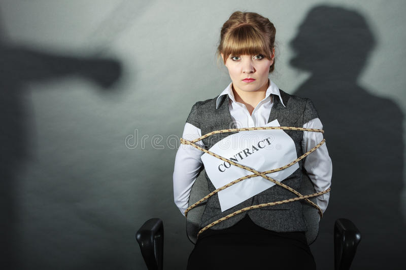 Upset businesswoman bound by contract terms. Upset businesswoman bound by contract terms and conditions. Helpless woman tied to chair become slave. Human shadow stock images