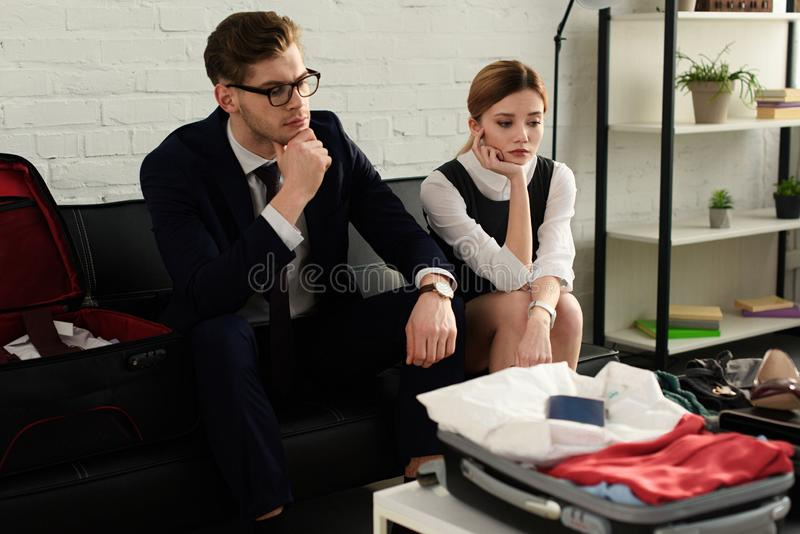 upset businesswoman and businessman couple looking on travel bag royalty free stock photos